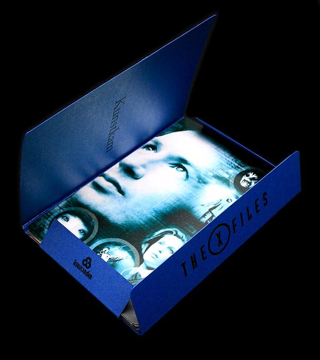 Коллекционные открытки X-Files. 9 завершённых сезонов, 9 открыток, 9 цветов. Открытки: дизайнерский картон с кварцево-белым свечением, обложка: насыщенно-синего цвета с серебристыми вкраплениями. Округлость формы и умеренный блеск материалов. Антрацитово-чёрная текстурная обёртка